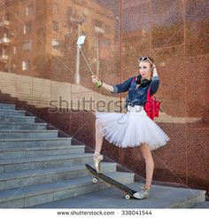 Girl listening to music on headphones. Cute ballerina makes hipster selfie phone on selfie stick. A girl wearing tutu, ballet shoes and sneakers, sunglasses. Girl riding on skateboard. Soft focus