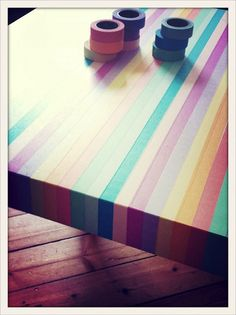 Washi tape rainbow table. This would be cool as a bench top in the kids crafting desk cupboard. Seal it?