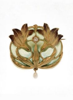 SANDOZ | AN ART NOUVEAU ENAMEL, PEARL AND GOLD BROOCH. The oval plaque designed as two purple, yellow and green enamel irises with gold scrolling leaves, with a pearl accent, on a green plique-à-jour enamel background, intact, suspending a pearl drop, circa 1900.