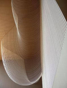 """Paredes+Alemán Arquitectos. Catenary Veil. Made out of 2.8 kilometers of bead-chain curves of different length, all taking their shape through gravity. The nickel-plated, steel catenaries were hung by their own weight from four hundred different coordinates, and distributed on the two perpendicular planes of the ceiling and adjacent wall.  Again people have already given it a new name:  """"the water drop""""."""