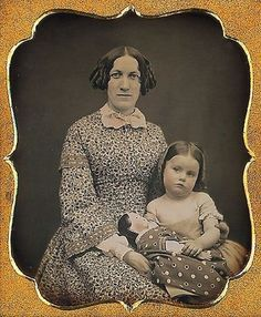 Antique photo of a mother, her little girl and her doll, circa 1860 - 1890.