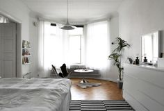 Black and white bedroom. A Finnish home, typical Scandinavian style with design classics and some IKEA thrown in. Lots of natural light, white curtains