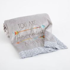 """""""You Are Our Greatest Adventure""""  Blanket has a grey velour front featuring a detailed arrow embroidery and a grey ikat pattern on the back. Perfect for stroller rides, bundling or simply a boho accent to the nursery."""
