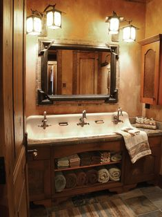 A cast-iron trough sink with three faucets adds antique flair to this warm, rustic bathroom. Four layered lanterns provide ample light, highlighting the stone countertop, wood vanity with towel storage and stone floor.