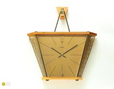 MID CENTURY ATLANTA JUNGHANS GERMANY WALL CLOCK! Mid Century design at its best! An amazing clock by west German clock manufactury ATLANTA. Trapezoid timepiece with an integrated hanging system. Absolutely period typical material mix of Palisander wood and solid brass elements. Interesting blanked-out modernistic pattern in the brass elements. The dial is minimalistic designed with fine stab indices and elegant golden polished appliqued indices 6 and 12. A modernistic statement!   Represents…