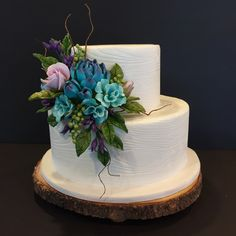 Gumpaste roses, succulents, filler flowers with ivory wood grain fondant tiers. Handmade by Kathy Peterson
