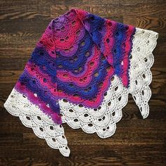 "A crocheted shawl in bi pride colours (Knit Picks' Chroma fingering yarn in colourway ""Lupine"")"