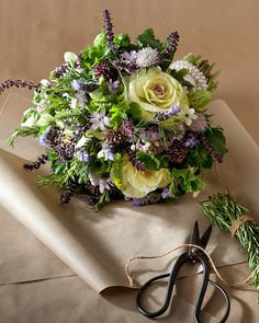 This bouquet has Ornamental oregano, lavender, rosemary, white kale, lavender hyacinth, flowering onions, white sweet pea, scented geranium, blue scabiosa, star of Bethlehem, and honey myrtle wrapped in ivory lace and a string of vintage pearls.