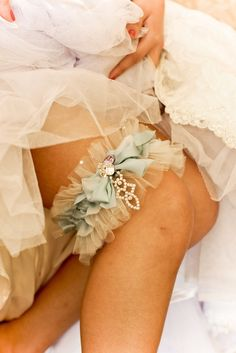 Delicate silk and tulle combine together to create this pretty ruffled garter. Swarovski crystals of different shapes and colors combine to decorate the center of the bow as well as provide the base for the drop pendant. An extra toss garter is included.