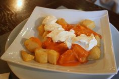 Patatas bravas with the traditional bravas sauce and also alioli sauce. A must try in Madrid!