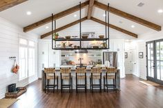 The industrial feel of the vent hood and stainless steel appliances was warmed and balanced by these walnut stained wooden beams and hardwood floors.