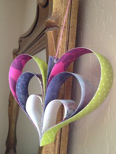 Lovely three dimensional hearts made from colorful scraps of leftover scrapbooking paper. Perfect for rainy day crafts or holiday decorations. These hearts look darling hanging anywhere and any time.