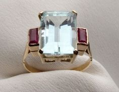 Circa 1950. This beautiful Mid 20th Century 18KT yellow gold ring is centered by a lovely 4.45 carat Emerald aquamarine stone and accented by two baguette cut rubies. The rubies have a .25 carat total ruby weight. The Retro ring measures 11.95mm wide and 7.56mm tall. The base of the shank measures 1.94mm wide and .64mm thick.