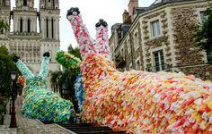 Florentijn Hofman est un artiste contemporain allemand. Il travaille sur des représentations géantes inspirées de la société de consommation. « Slow Slugs » est le nom de sa nouvelle installation présentée à Angers. On peut y voir des limaces géantes, composées de 40 000 sacs plastiques, gravir les marches qui mènent à une église, signifiant la mort et l'asphyxie lente de notre société d'hyper consommation.