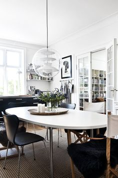 Kitchen. Home of Danish designer Line Nevers Krabbenhøft, Frederiksberg, Denmark. Chairs: Series 7 by Fritz Hannsen and safari chairs by Carl Hansen & Søn. Lamp: Globe by Verner Panton. Table: CH323 by Wegner.