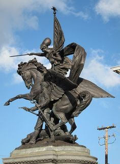 Spanish-American War Memorial, Dolores Street, San Francisco, California. Called California Volunteers, this bronze sculpture by Douglas Tilden, shows an American soldier, with pointed gun in one hand and a sword in the other, standing over a fallen comrade, a cannon nearby. Above them the goddess of war, Bellona, is astride the winged horse Pegasus.