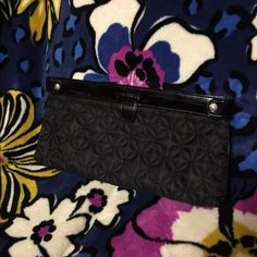 Vera Bradley Limited-Edition Midnight Clutch Black exterior. Adorably patterned interior. Patent trim. Measures 13  x 5.5  x .5 inches. Inside, two slip pockets and one zippered pocket. In excellent condition, NWOT. One small imperfection, almost unnoticeable, smaller than 1/8th of a penny as shown. Vera Bradley Bags Clutches & Wristlets
