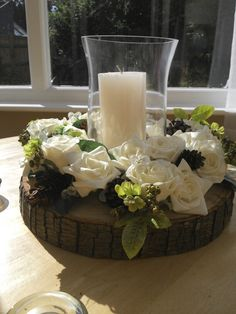 Handmade wedding table centres with foam rose wreath, tree slice, hurricane vase and a few pinecones