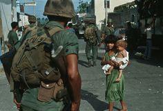 1982 En la foto una niña sonríe a la cámara y carga a un niño visiblemente desnutrido