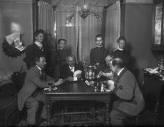 HISTORIC PHOTO - Poker night with the boys was a bit different in 1910. An intimate group of friends gather in the home of Grand Island photographer Julius Leschinsky to play a friendly game of cards and share a glass of wine in a photo from Stuhr's collection. Julius Leschinsky is the fourth man from the left and his wife Minnie is the third woman from the left. This photograph was likely taken in about 1910.