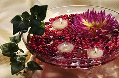 glass bowl filled with water, berries and floating candles
