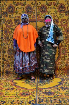 Picture of two musicians in a group called Poetic Pilgrimage, dressed in colorful clothes standing in front of a yellow patterned backdrop