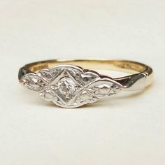 This lovely art deco ring is c.1940s. The band is 9k yellow gold with a Platinum setting in a beautiful milgrain detailed geometric shape holding a diamond at the center. The diamond measures approximately 2.4mm and the setting measures 14mm x 5.8mm. The band is 2.2mm around the back, very