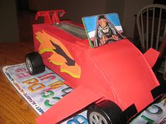 Race car Valentine mailbox made out of tissue box, cardboard, paint, and parts from an old toy truck.