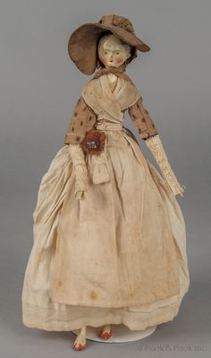 """Carved and painted wooden peg doll, mid 19th c., retaining her original clothing, 15"""" h."""