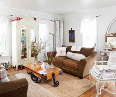 An antique railroad cart-turned-coffee table anchors the living room! Get more antique farmhouse looks here: http://www.bhg.com/decorating/decorating-style/country/house-tour--antique-farmhouse/?socsrc=bhgpin110414antiqueliving&page=2