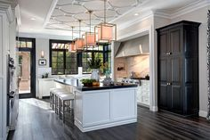 White Transitional Chef Kitchen designed by Tatiana Machado-Rosas, with Large Islandhide Stately and sophisticated, this kitchen creates a graceful mood with a white palette, subtle pink accents and lots of natural light courtesy of large windows and a glass door. The oversized island offers casual eating as well as plenty of prep space.