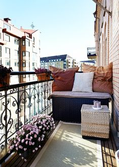 Cute balcony with a little bench and some flowers. I love outdoor rugs on balconies.