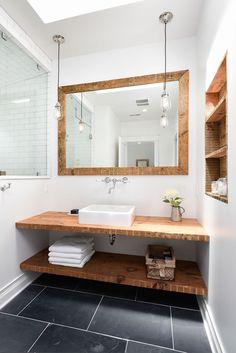 Slate flooring and a custom vanity of reclaimed wood hita subtle nautical note inthe master bath.
