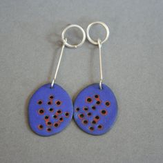 Enamel earrings that look a bit like rusty, painted metal. Unique.  The hand cut copper piece is enameled on both sides and etched to a smooth. semi- matte finish that allows the copper colors to peek out around the holes like rust. The wire is all sterling silver.  The earrings are 2.75 long from the post. Fun to wear! The earrings swing and bobble a bit when you walk. Posts and over-sized clutches are sterling silver.  Earrings are made to order, but will look very much like these. Please…