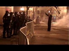 OccupyOakland protests - Navyman stands in tear gas.filled Police Firestorm