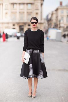 Inspiração street style look com saia mídi preta e branca, top preto de manga longa, scarpin nude, maxi clutch branca e óculos escuros.