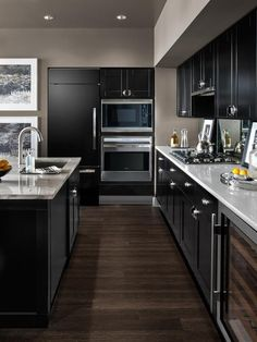 The refrigerator is cleverly concealed behind a cabinetry panel, and a dual-zone wine storage cabinet offers space for up to 46 bottles. Stainless steel accents and cherry wood-faced shelves complement the kitchen's design aesthetic.