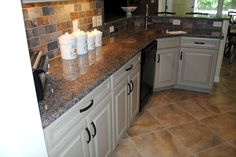 "Maple Cabinets in ""Celadon"" Paint w/ Chocolate Glaze New Caledonia Granite w/ 3/8 RO Edge Mirabelle Sink, Moen Brandford Faucet Muticolored ""Slate Look"" Backsplash 18"" x 18"" Tile Floor"