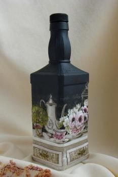 What looks like a Jack Daniels bottle or similar painted and decoupaged to make a charming accessory.