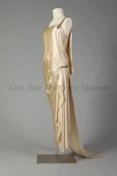 "1920s / House of Worth / French /White satin wedding dress. Dress with dropped waist and ""diamond"" shoulder straps, side panel clasp at hip with diamond, back with center panel falling free from hips to train, draped and wrapped front."