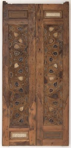 The pair of doors bears a symmetrical geometric design with small  star-shaped or polygonal plaques, each decorated with an arabesque. Two  panels which carr...