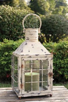 "This cream lantern measures 10"" square and 21"" tall to top of handle. Features a door with a latch to access candle and other items inside the lantern. Top is open to allow for ventilation. Comes in a"