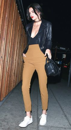 Kendall Jenner wears a moto jacket, bodysuit, high-rise trousers, and white sneakers