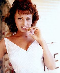 Brunette Italian actress Sophia Loren poses with a flower in her mouth wearing a white dress
