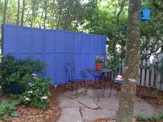privacy fence made from old shutters painted blue