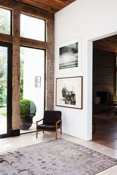 A vintage Chinese rug and a Danish chair Kayne's husband owned when they first met are simple comforts warming up the expansive foyer.  Photos by Nicole Lamotte via One Kings Lane