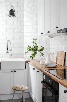 Białe kafle w kuchni wpisują się w skandynawski styl, w jakim urządzono wnętrze. W zestawieniu z drewnem podkreślają...
