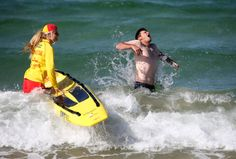 The Los Angeles Dodgers' Drew Butera, right, grimaces as he is splashed with water while surf lifesaver Sophie Thomson holds a rescue board at Bondi Beach in Sydney, Wednesday, March 19, 2014. The Major League Baseball season-opening two-game series between the Los Angeles Dodgers and Arizona Diamondbacks in Sydney will be played this weekend. (AP Photo/Rick Rycroft)