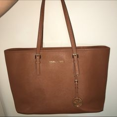 Authentic Michael Kors travel tote Tan MK travel tote, never used, and in perfect condition. No scratches, or wear. Make an offer. Michael Kors Bags Shoulder Bags