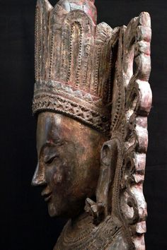 Standing Buddha on a lotus base in majestic attire. Right hand in varada mudra, left hand holding one end against his chest. Material: wood with remains of lacquer. Height: 187 cm. The crowned Buddha image, was popular in contemporary Eastern India artistic traditions which exercised a strong influence on the Pagan school.